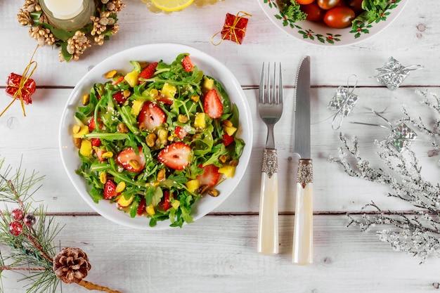 Salat mit rucola, erdbeeren und ananas mit weihnachtsdekoration