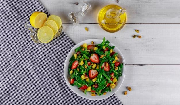 Salat mit rucola, erdbeeren und mango mit olivenöl und zitrone