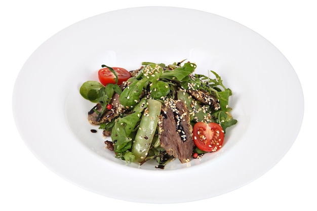 Salat mit rucola und dünn geschnittenem rindfleisch auf weiß um den servierteller, lokalisiert auf weißem hintergrund.