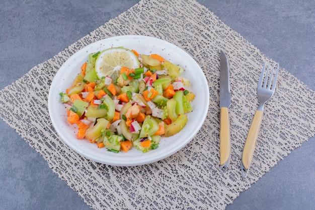 Salat mit saisonalen kräutern und gemüse in einer platte