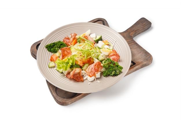 Salat mit salat, croutons, zwiebeln und gebratenem speck auf originalplatte und schreibtisch lokalisiert auf weißem hintergrund