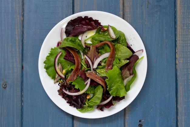 Salat mit sardellen und zwiebel auf weißer platte auf blauer oberfläche