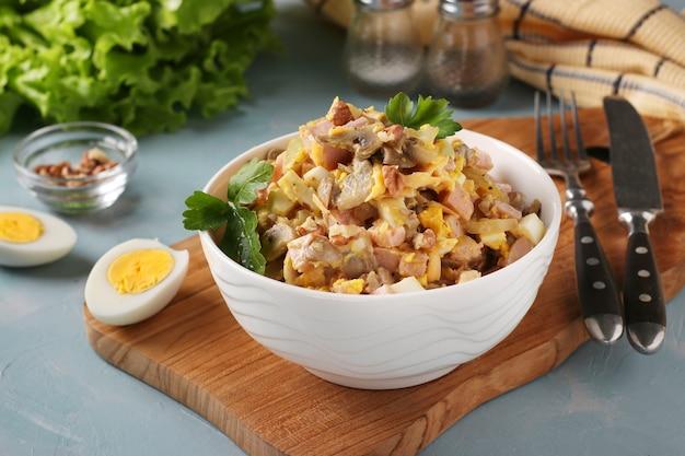 Salat mit schinken, eiern, zwiebeln und pilzen in einer weißen schüssel auf holzbrett