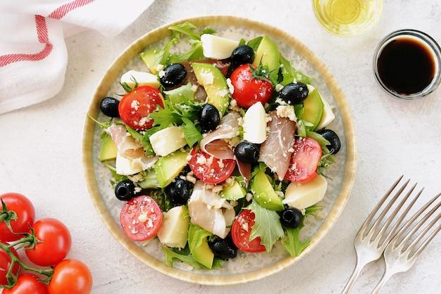 Salat mit schinken, mozzarella, avocado, kirschtomaten, schwarzen oliven und parmesan