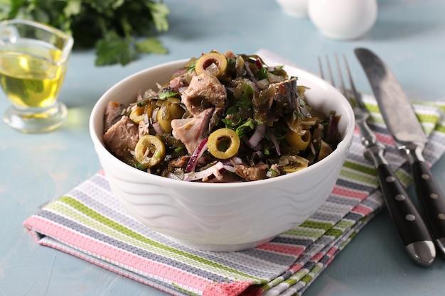 Salat mit seetang, thunfischkonserven und oliven in weißer schüssel auf hellblauem hintergrund. querformat. nahaufnahme