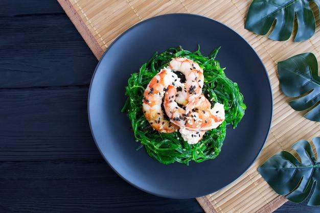 Salat mit seetang und roten garnelen in der dunklen platte auf der tropischen oberfläche.
