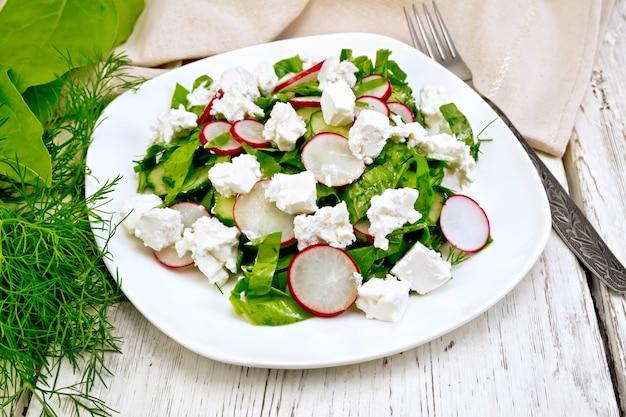 Salat mit spinat, gurken, rettich und gesalzenem käse, dill und frühlingszwiebeln in einem weißen teller, ein handtuch auf dem hintergrund eines holzbretts