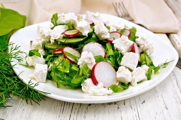 Salat mit spinat, gurken, rettich und gesalzenem käse, dill und frühlingszwiebeln in einer schüssel, handtuch auf dem hintergrund eines hellen holzbretts