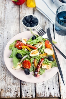 Salat mit stücken gebratenem halloumi-käse, rucola-blätter, salat, oliven, gegrillter tomate und pfeffer auf teller. ausgewogenes gesundes essen, ein griechisches rezept für sauberes essen.