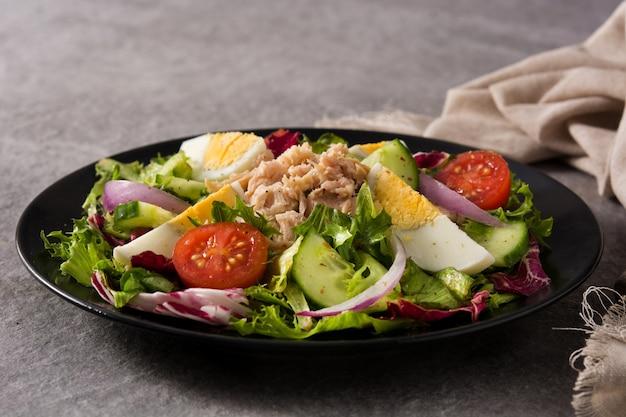 Salat mit thunfisch, ei und gemüse auf schwarzblech und grau