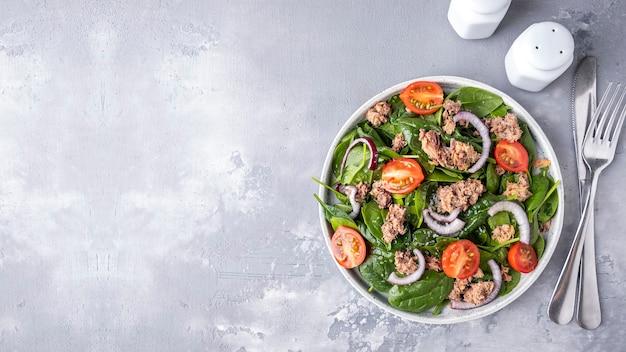 Salat mit thunfisch, spinat und tomaten. draufsicht, textraum