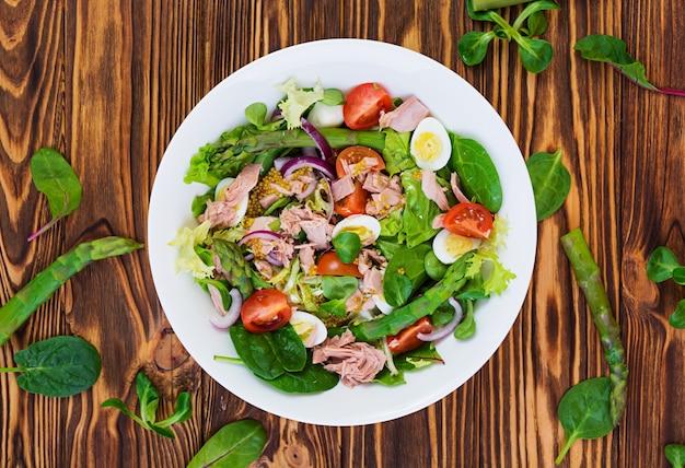 Salat mit thunfisch, tomaten, wachteleiern, spargel und zwiebeln auf holz