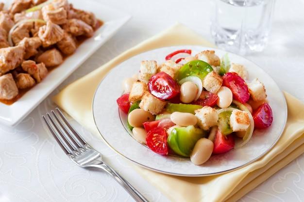 Salat mit tomaten, gekochten weißen kidneybohnen und croutons aus weißbrot,