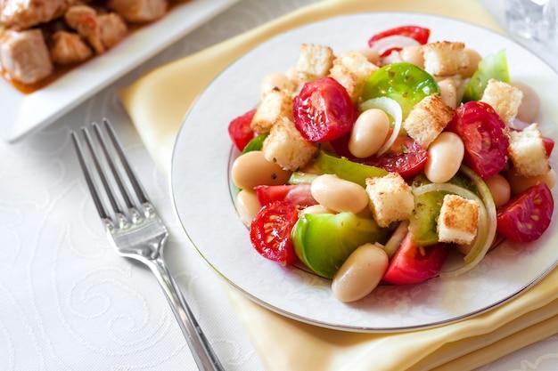 Salat mit tomaten, gekochten weißen kidneybohnen und croutons aus weißbrot