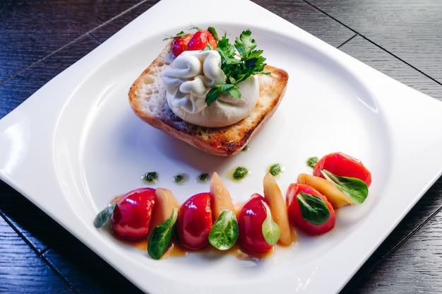 Salat mit tomaten, honigbirne und burrata-käse mit basilikum und olivenöl auf holzoberfläche
