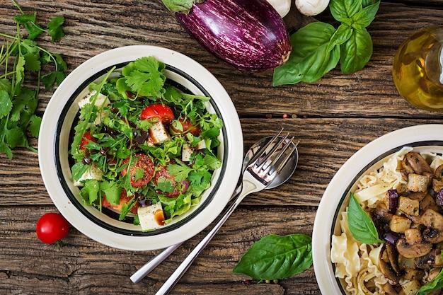 Salat mit tomaten, käse und koriander in süß-saurer soße. georgische küche. gesundes essen. ansicht von oben. flach liegen
