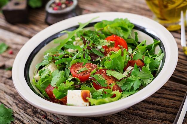 Salat mit tomaten, käse und koriander in süß-saurer soße. georgische küche. gesundes essen.