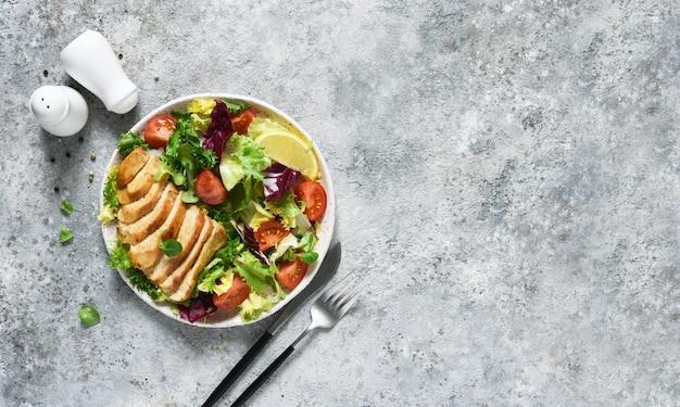 Salat mit tomaten und hähnchenfilet in einem teller mischen.