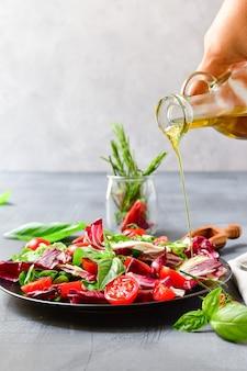 Salat mit tomaten und radicchio-blättern, basilikum mit olivenöl und rosmarin. olivenöl gießen