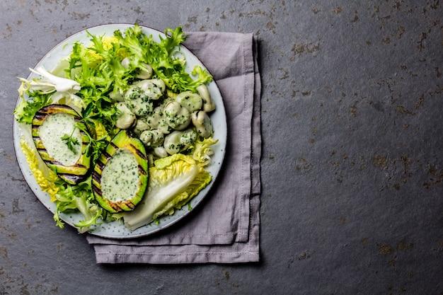 Salat mit vegetarischen salatbohnen mit gegrillter avocado- und kräutersoße. ansicht von oben