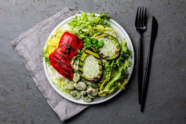Salat mit vegetarischen salatbohnen mit gegrillter avocado und paprika.