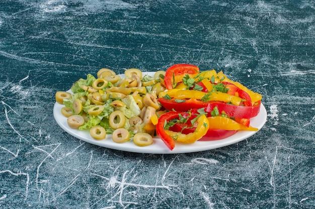Salat mit verschiedenen zutaten wie kirschtomaten, kräutern und gewürzen.