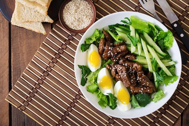 Salat mit würzigem rindfleisch, gurke und eiern im asiatischen stil.