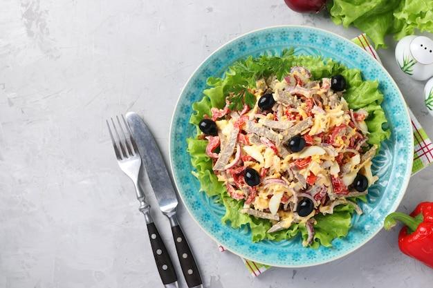 Salat mit zunge, paprika, eiern, salat, käse und schwarzen oliven auf blauem teller auf grauer oberfläche. draufsicht. platz für text