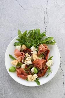 Salat rucola, parmaschinken mit getrockneten tomaten, mozzarellascheiben, croutons, kapern, gewürzöl und gewürzen spice