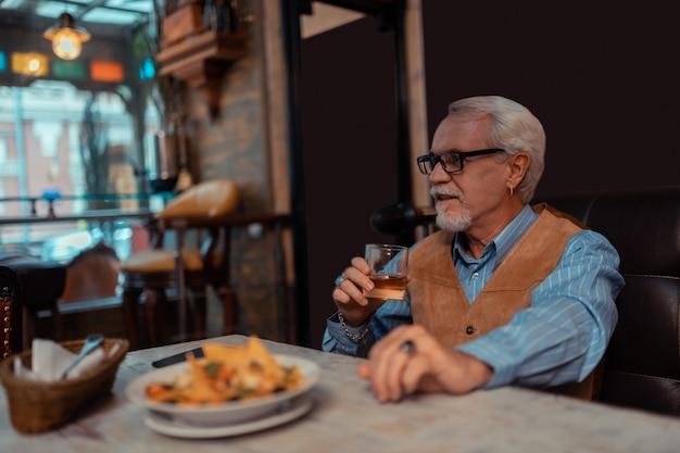 Salat und whisky. grauhaariger bärtiger mann, der alleine im restaurant salat isst und whisky trinkt