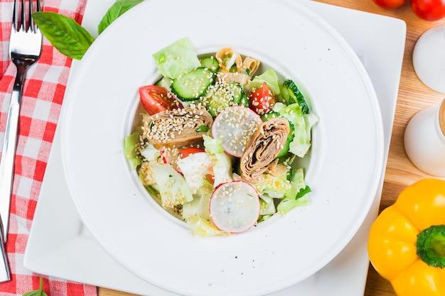 Salat von frischem gemüse mit gebratener pfannkuchenrolle