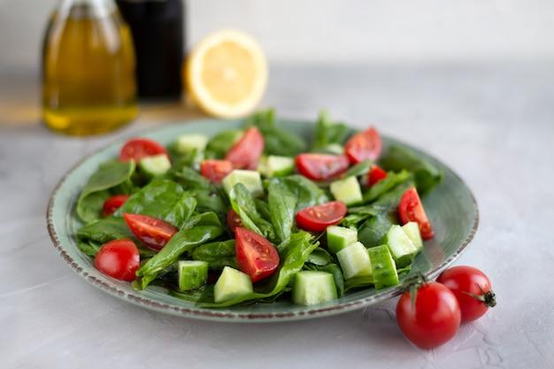 Salat von grüns, gurken, kirschtomaten in einer grünen platte