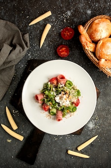 Salat von gurken, tomaten, schinken mit geriebenem parmesan bestreut