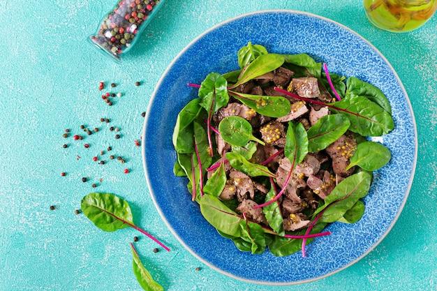 Salat von hühnerleber und blättern von spinat und mangold. draufsicht der flachen lage