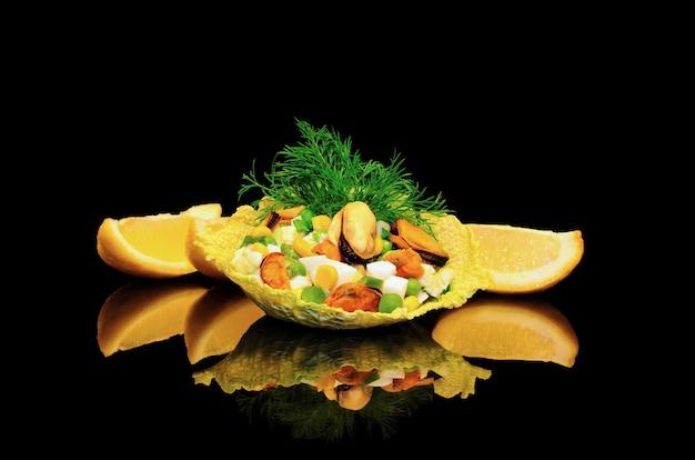 Salat von muscheln mit mais und erbsen in den blättern von wirsing auf schwarzem hintergrund