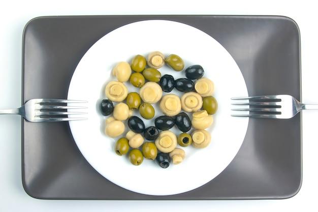 Salat von schwarzen und grünen oliven auf einem teller.