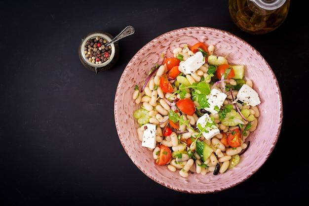 Salat von weißen bohnen, von tomate, von sellerie, von gurke, von arugula, von roter zwiebel und von feta in der schüssel