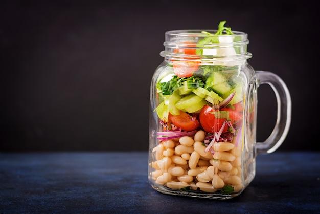 Salat von weißen bohnen, von tomate, von sellerie, von gurke, von arugula, von roter zwiebel und von feta in einem ja