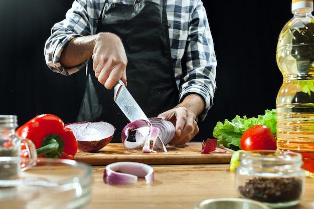Salat zubereiten. köchin, die frisches gemüse schneidet. kochvorgang. selektiver fokus. das gesunde essen, küche, salat, diät, küche bio-konzept