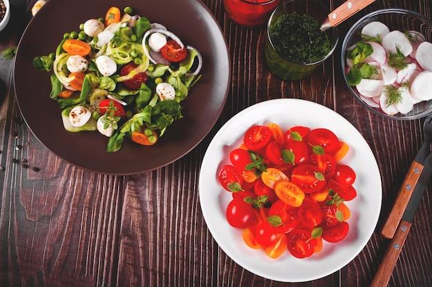 Salate aus frischen kirschtomaten mit basilikum, mozzarella, gemüse und rettich auf dem esstisch