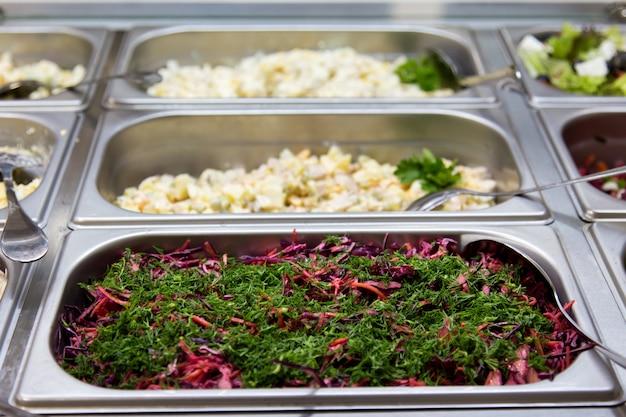 Salate im restaurant auf den metallplatten. selektiver fokus