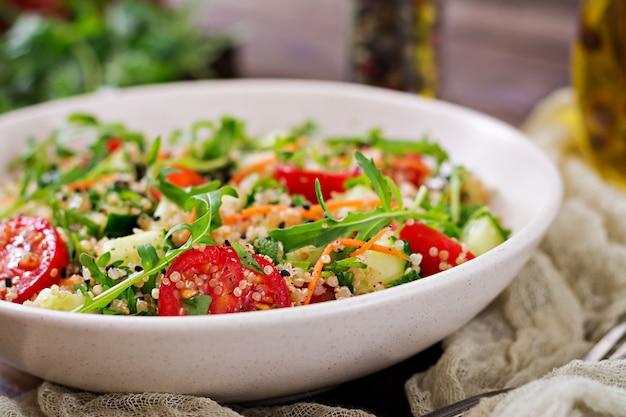 Salate mit quinoa, rucola, rettich, tomaten und gurke in der schüssel auf holztisch. gesundes lebensmittel-, diät-, detox- und vegetarierkonzept.