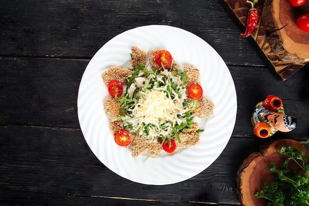 Salatgemüse und gebratenes huhn in sesam