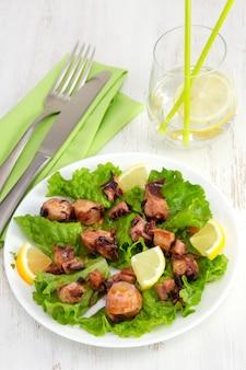 Salatkopfsalat mit krake auf der platte und dem glas wasser