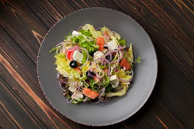 Salatmischung mit lachs, feta, zwiebeln und oliven auf einem teller auf einer holzoberfläche