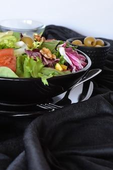 Salatplatte mit salat, tomaten, oliven und öl. auf einem schwarzen tuch
