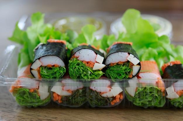 Salatrolle mit krabbe im plastikkasten für das gesunde essen