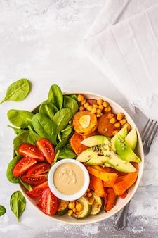 Salatschüssel des strengen vegetariers mit dem gebackenen gemüse, kichererbsen, avocado und tahini, die auf einem weißen hintergrund ankleiden