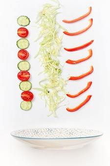 Salatschüssel mit fallendem gemüse
