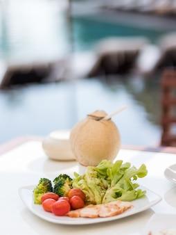Salatteller mit kokosnusssaft auf einem tisch